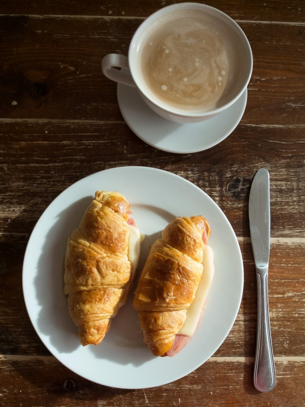 Ham and cheese croissant overhead with coffee long