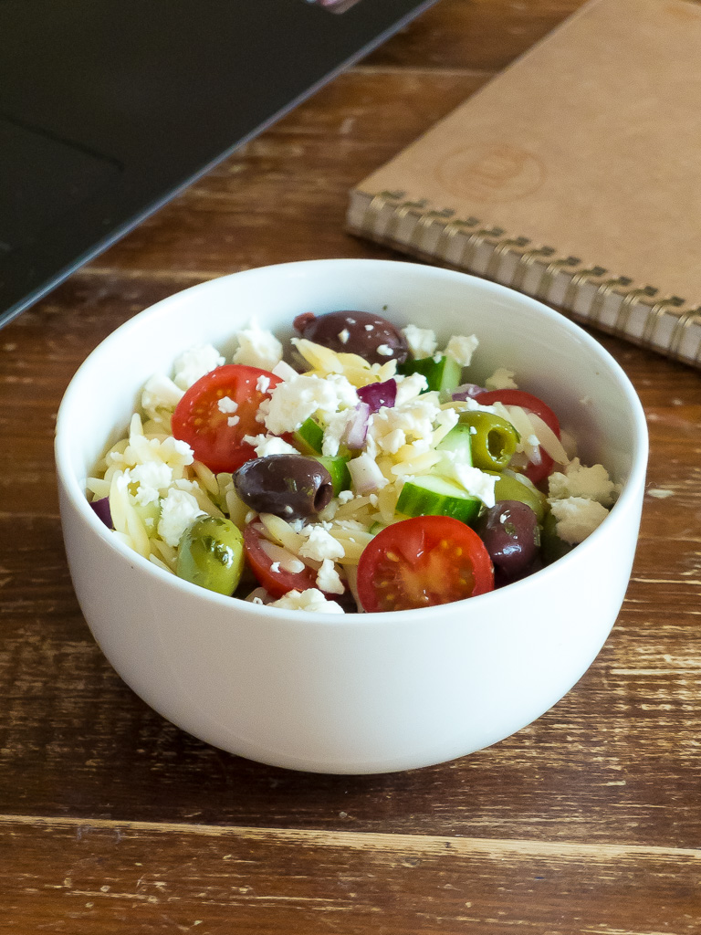 greek salad with orzo by a laptop and notebook