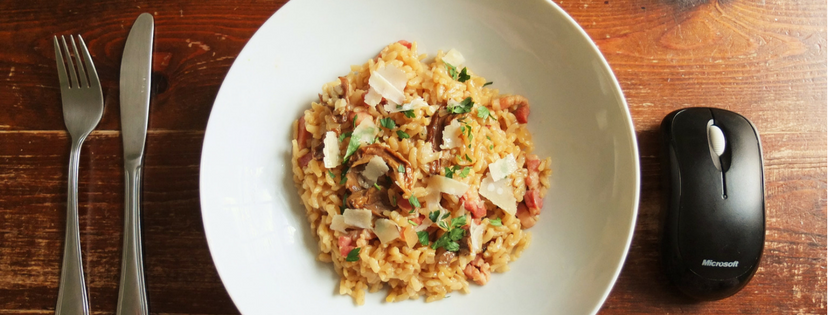 bowl of risotto with mouse, knive and fork