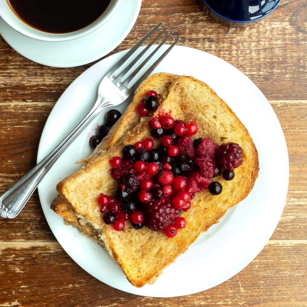 French toast with berries, coffee and fork